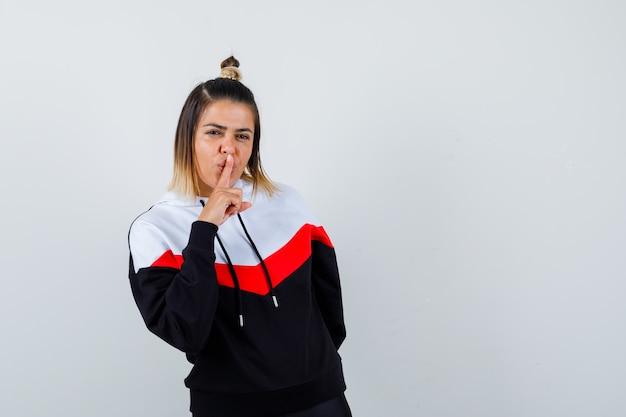 Señorita en suéter con capucha mostrando gesto de silencio y mirando confiado