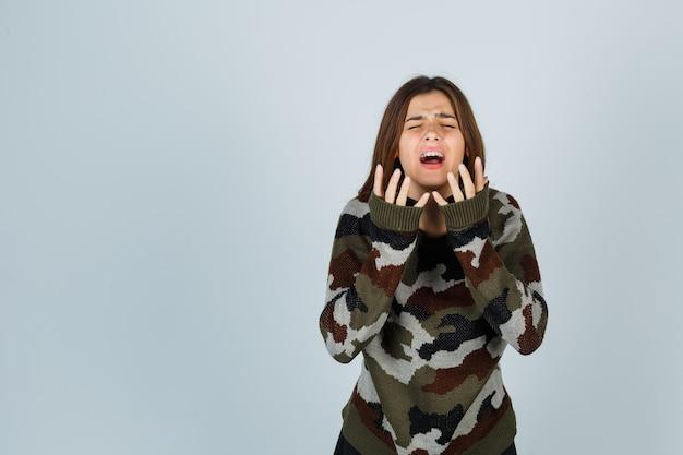 Señorita en suéter cogidos de la mano cerca de la cara, llorando y mirando triste