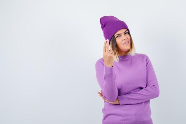 Señorita en suéter morado, gorro mostrando gesto de pistola y mirando confiado, vista frontal.