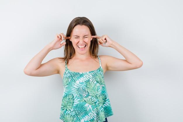 Señorita taponando los oídos con los dedos y mirando molesto. vista frontal.