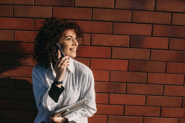 Señorita tener una conversación telefónica mientras posa en un muro de piedra con algunos aparatos modernos
