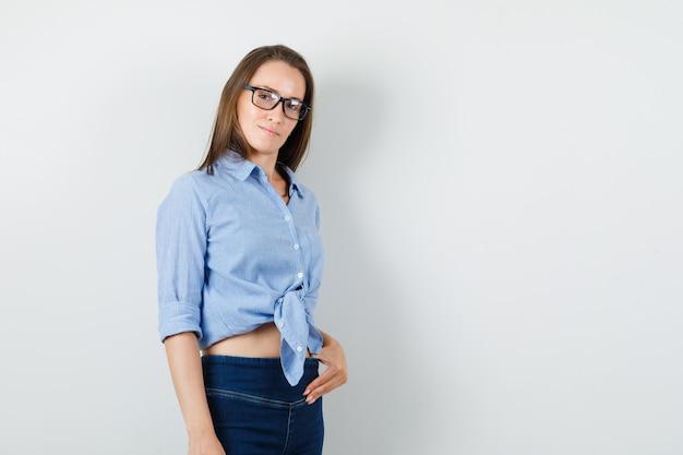 Señorita tocando sus pantalones y sonriendo con camisa azul