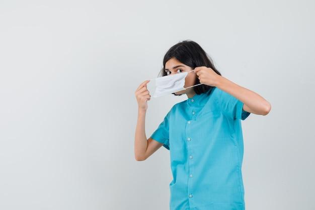 Señorita vistiendo una mascarilla blanca con camisa azul y mirando listo