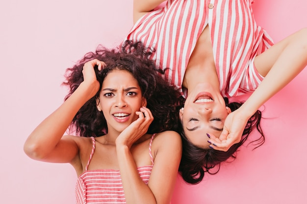 Señoritas con hermosos ojos marrones y lindo maquillaje, vestidas con ropa de diseñador de moda de color rosa