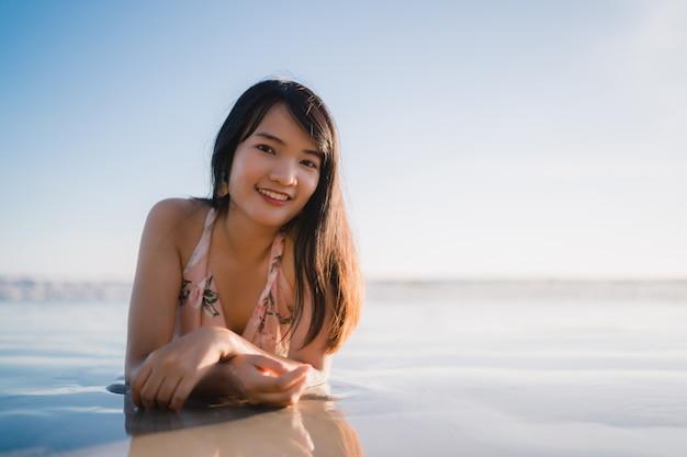 Sensación asiática joven de la mujer feliz en la playa, feliz femenino hermoso relaja la diversión sonriente en la playa