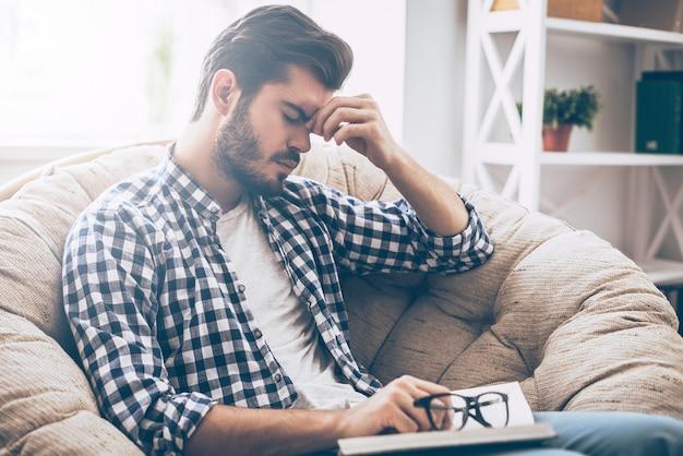 Sensación de cansancio. hombre joven frustrado que sostiene un libro y se masajea la nariz mientras está sentado en una silla grande en casa y mantiene los ojos cerrados