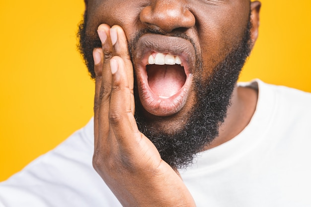 Sensación de dolor de muelas. frustrado joven africano tocando su mejilla y manteniendo los ojos cerrados