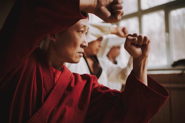 Sensei en rojo dos estudiantes de artes marciales entrenando