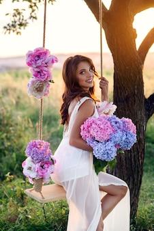 Sensual chica hermosa con una sonrisa perfecta en un vestido blanco sentada en un columpio de madera con un ramo de flores de colores tiernos.