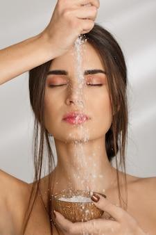 Sensual dama con los ojos cerrados vertiendo sal exfoliante corporal.