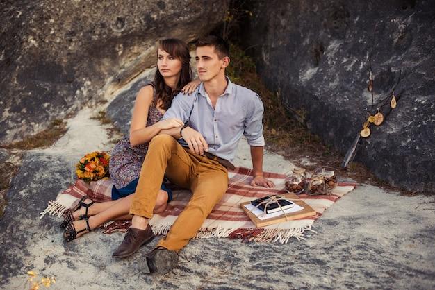 Sensual encantadora pareja en cálidos abrazos en ropa casual sentado en la tela escocesa en la roca con decoración de otoño.