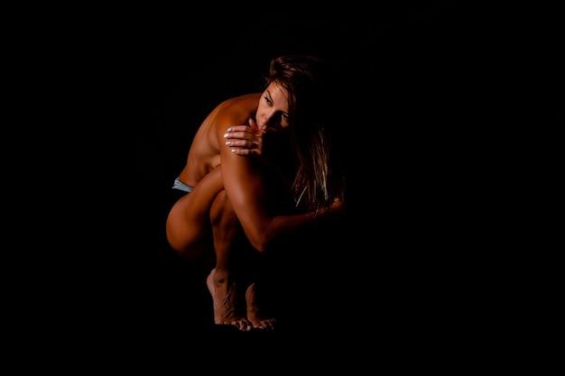 Sensual joven en topless con los ojos cerrados sobre fondo negro hermosa chica de cuerpo desnudo