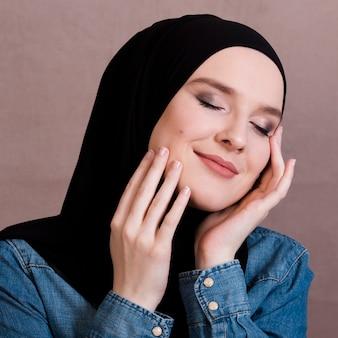 Sensual mujer árabe tocando sus mejillas contra la superficie de color
