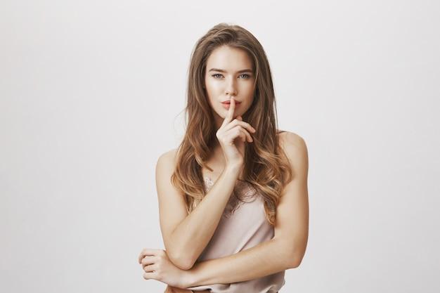 Sensual mujer calla, presiona los dedos sobre los labios