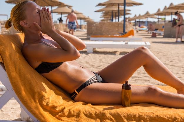 Sensual mujer delgada aplicando aceite bronceador