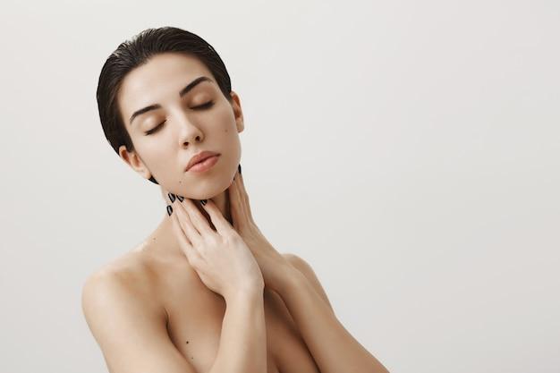 Sensual mujer femenina desnuda de pie con los ojos cerrados, tocando el cuello suavemente