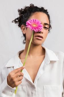 Sensual mujer con flor cubriendo ojo.