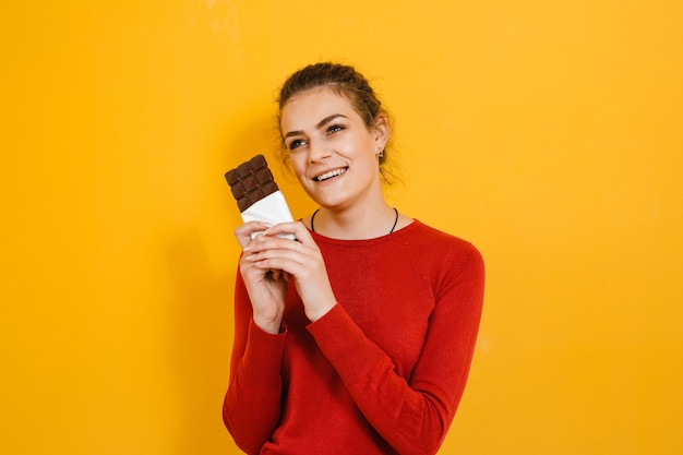 Sensual mujer joven atractiva comiendo y es chocolate asombrado aislado sobre pared amarilla
