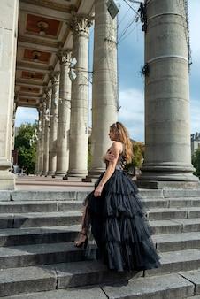 Sensual mujer joven y bonita en vestido de noche cóctel negro posando cerca de la entrada del teatro de la ciudad con columnas blancas