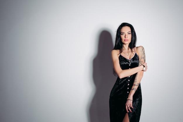 Sensual mujer morena en elegante vestido negro sobre fondo gris.