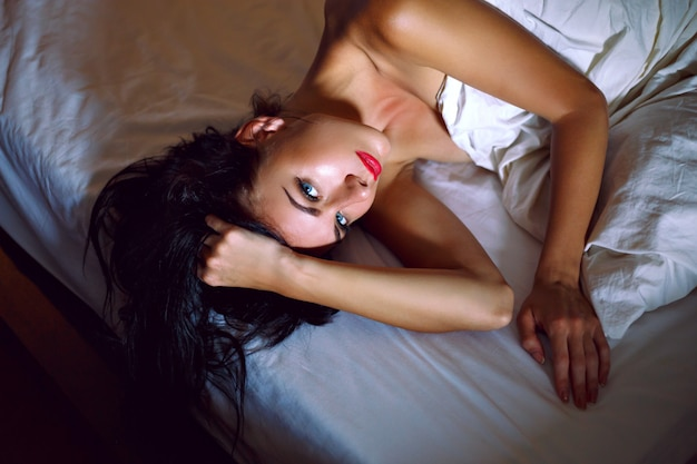 Sensual mujer muy elegante con largos cabellos morenos y piel bronceada perfecta, acaba de despertar y acostado en la cama en un hotel de lujo, perfecto momento de relajación por la mañana.