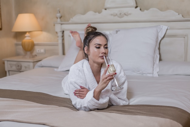 Sensual mujer oliendo champán en la cama