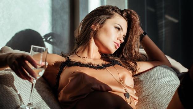 Sensual mujer sexy posando en su habitación bebiendo una copa de champagne sparkle vine y celebrarla