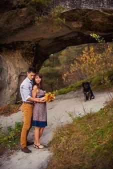 Sensual pareja encantadora en abrazos cálidos en ropa casual que se queda cerca de la roca con perro negro