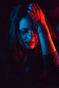 Sensual retrato de hermosa niña detrás de un vidrio con gotas de lluvia con iluminación azul rojo