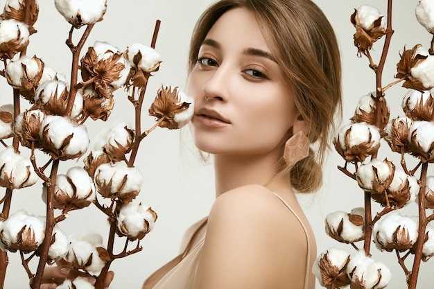 Sensual retrato de modelo de mujer glamour entre ramitas de algodón