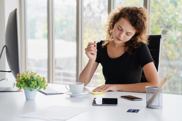 La sentada atractiva joven de la mujer y toma nota sobre negocio mientras que trabaja en escritorio de oficina