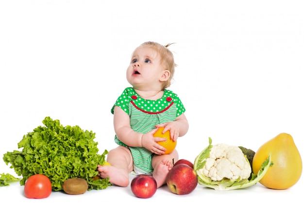 Sentada del bebé rodeada por las frutas y verduras, aisladas en blanco