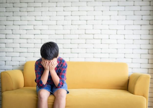 Sentada triste del muchacho asiático que se sienta en el sofá