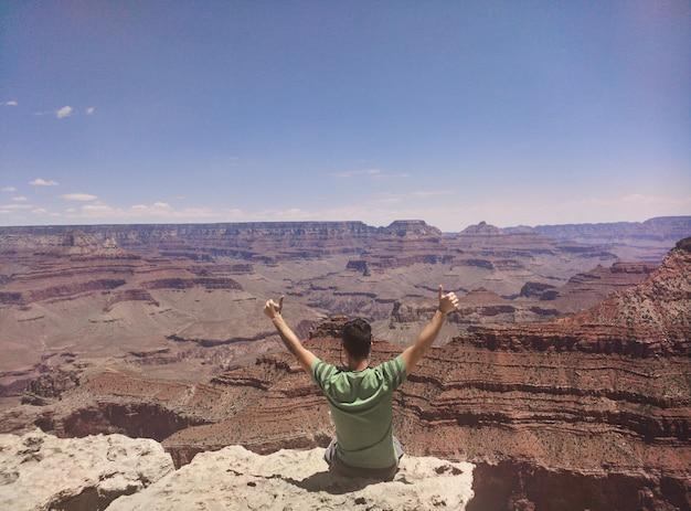 Sentado al borde de un descenso profundo en el hermoso parque nacional del gran cañón