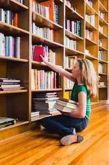 Sentado en la chica del piso poniendo el libro en el estante