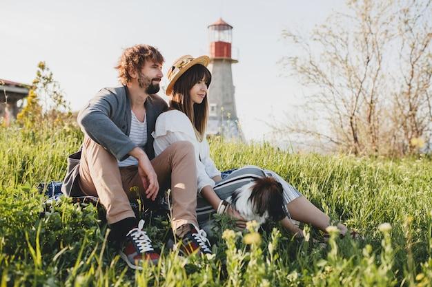 Sentado en la hierba joven elegante hipster pareja enamorada caminando con perro en el campo, moda boho de estilo veraniego, romántico