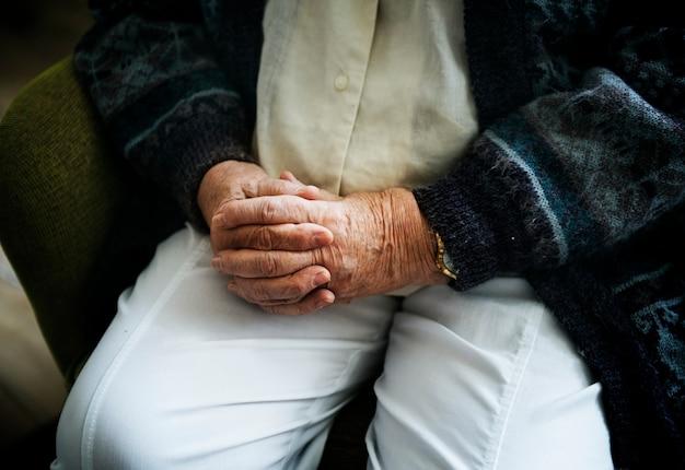 Sentado hombre senior de cerca en sus manos de la mano