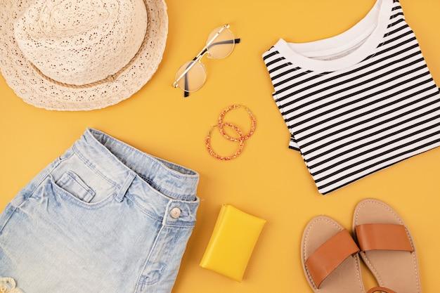 Sentar planas con accesorios de moda de mujer, pantalones cortos de jeans, sombrero, gafas de sol sobre pared amarilla. moda, blog de belleza online, estilo de verano, concepto de compras y tendencias. vista superior