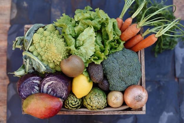 Sentar planas de una canasta de verduras orgánicas sobre un fondo de pizarra