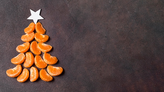 Sentar planas de forma de árbol de navidad de mandarinas con espacio de copia