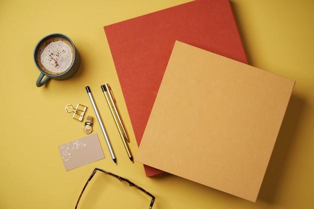 Sentar planas con libros, taza de café, gafas de lectura, bolígrafo y lápices en amarillo.