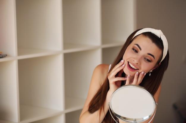 Sentarse en casa, mirarse al espejo, reír y divertirse. régimen de cuidado de la piel por la mañana.