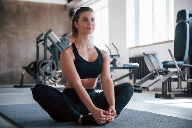 Sentarse y descansar. foto de hermosa mujer rubia en el gimnasio en su fin de semana
