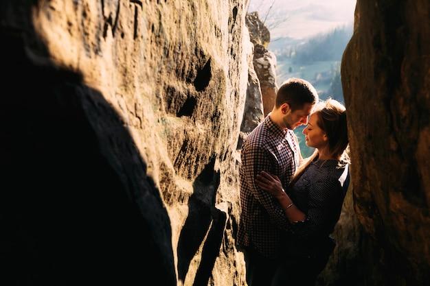 Sentimental feliz pareja de enamorados unidos rodeados de rocas