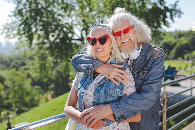 Sentimientos románticos. buen hombre positivo abrazando a su esposa mientras está de pie con ella en el puente