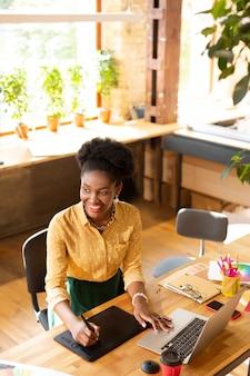 Sentirse bien. gerente creativo de piel oscura sonriendo mientras se siente bien y feliz trabajando todo el día
