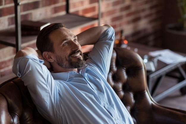 Sentirse bien. positivo feliz empresario barbudo sentado en el sofá y poniendo las manos detrás de la cabeza mientras disfruta de su relajación