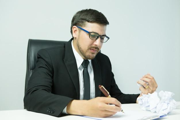 Sentirse cansado. hombre joven frustrado que mantiene los ojos cerrados y parece cansado mientras trabaja hasta tarde en su lugar de trabajo