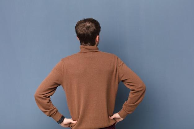 Sentirse confundido o lleno o dudas y preguntas, preguntándose, con las manos en las caderas, vista trasera