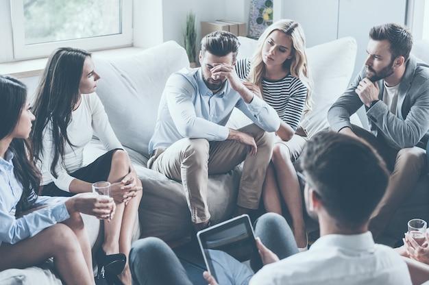 Sentirse deprimido. grupo de jóvenes sentados en círculo mientras un hombre sostiene la cabeza en la mano y parece molesto mientras la mujer joven lo consuela